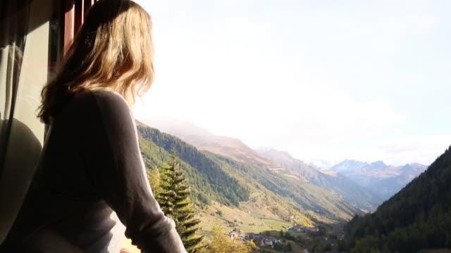 woman opens window shutters, look out to mountain scene - aussicht genießen stock-videos und b-roll-filmmaterial