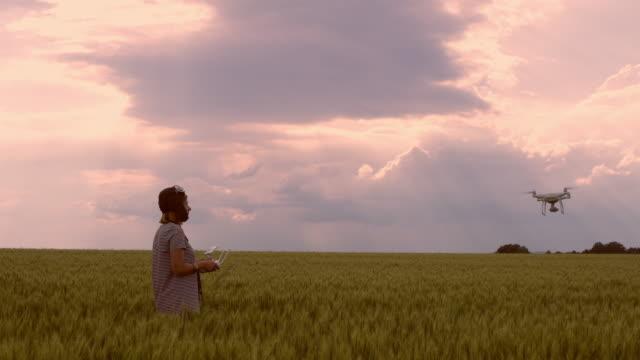 DS-Frau-Betrieb eine Drohne in der Landschaft bei Sonnenuntergang