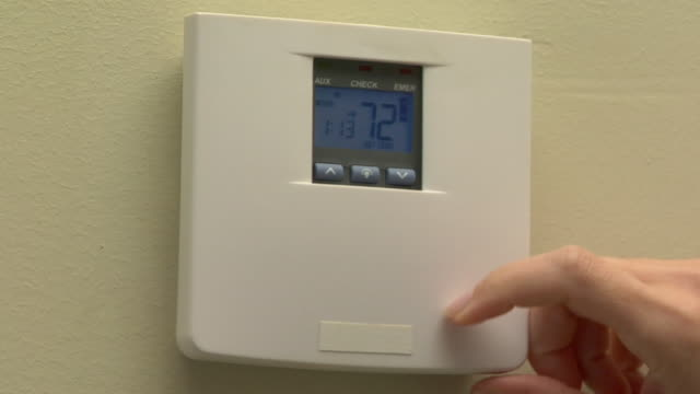 CU, Woman operating thermostat on wall, close-up of hand