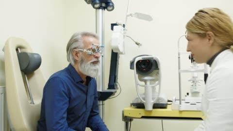 stockvideo's en b-roll-footage met vrouw oftalmoloog veranderende lenzen op de bril - lens oogbol