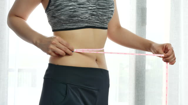woman or girl measuring her waist with tape at home - ribbon sewing item stock videos & royalty-free footage