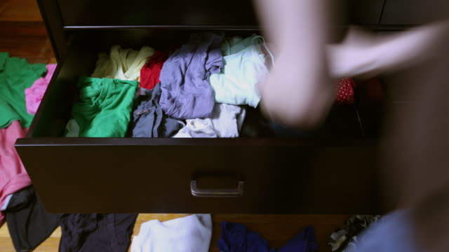 ms t/l woman organizing messy drawer full of clothes / new york city, new york, usa - wohnraum stock-videos und b-roll-filmmaterial