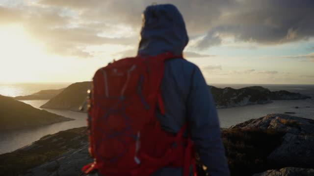 kvinna utomhus äventyr: vandring i norge, på berget vid en fjord - ryggsäck bildbanksvideor och videomaterial från bakom kulisserna
