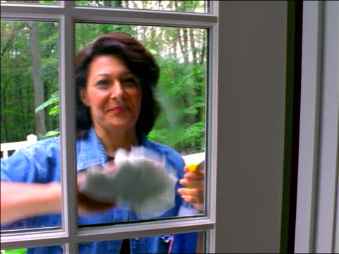 vídeos de stock e filmes b-roll de woman outside spraying + wiping window of door with cloth - só uma mulher madura