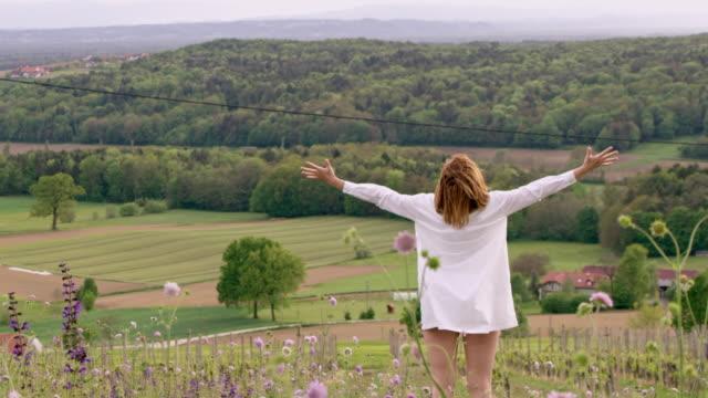 SLO MO DS femme tendant ses bras au sommet d'une colline