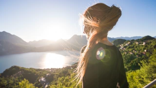 vídeos de stock, filmes e b-roll de mulher que negligencia o lago da montanha e a vila do lago em um dia de verão ensolarado - cidade pequena