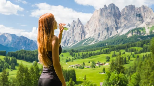 woman overlooking valley with mountains in background, hydrating from reusable water bottle - reusable stock videos & royalty-free footage