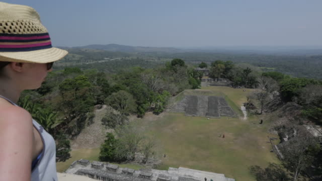 woman overlooks the xunantunich temple in belize - maya kultur stock-videos und b-roll-filmmaterial