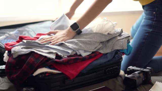 vidéos et rushes de vêtements de femme pack dans sac valise sur le lit, plein de vêtements dans sac, préparent à nouveau voyage et voyagent à long week-end. - plein