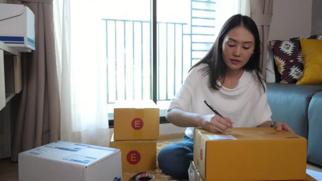 stockvideo's en b-roll-footage met vrouw verpakkingsdozen - karton