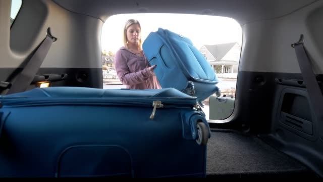 woman packing car with luggage. - boot stock videos & royalty-free footage
