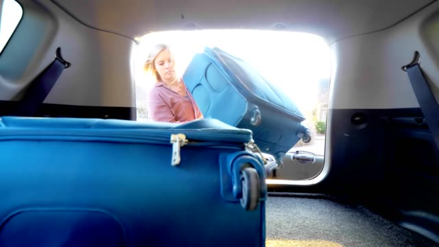 woman packing car with luggage. - bagaglio video stock e b–roll