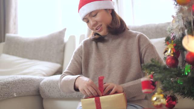 vídeos y material grabado en eventos de stock de mujer empacando regalo de navidad para el día de navidad - sólo mujeres jóvenes