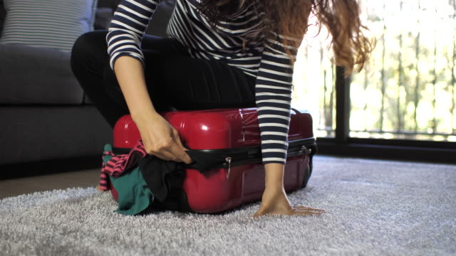 woman packing full suitcase - packing stock videos & royalty-free footage