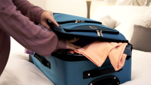 woman packing overfilled suitcase. - filling stock videos & royalty-free footage