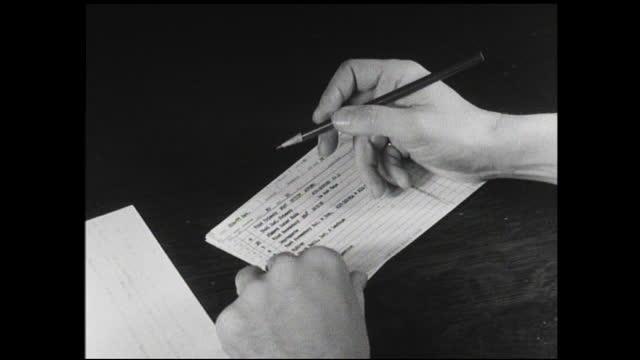 woman packing small parts inside box and hands with pencil circling lines on file card - 1940 1949 bildbanksvideor och videomaterial från bakom kulisserna