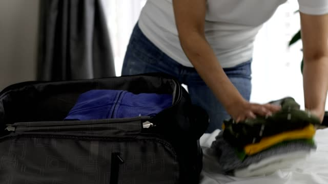 woman packing suitcase, adding clothes - bag stock videos & royalty-free footage