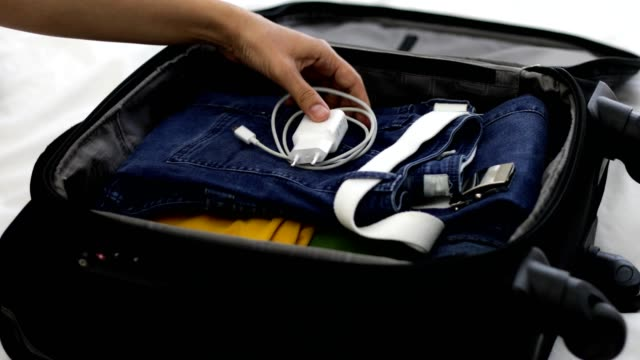 woman packing suitcase, adding phone charger - packing stock videos & royalty-free footage
