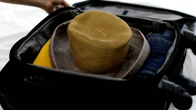 woman packing suitcase, adding sun hat. - hat stock videos & royalty-free footage