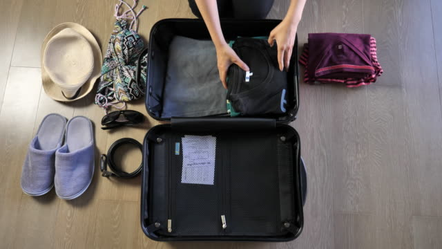 woman packing suitcase for a trip, top view - packing stock videos and b-roll footage