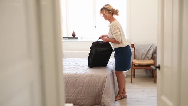 Woman packing suitcase in bedroom