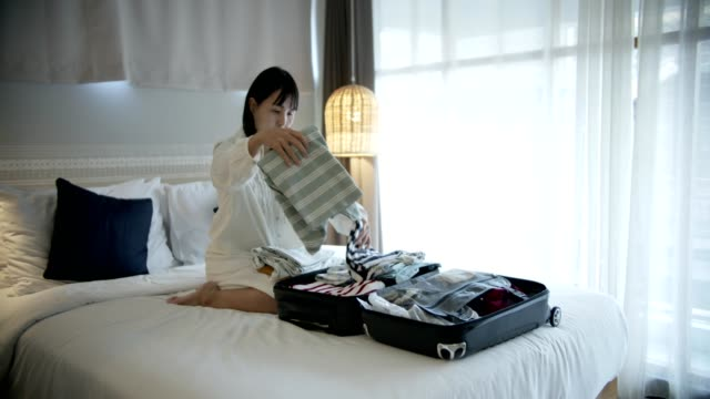 Woman packing suitcase in her bedroom at home