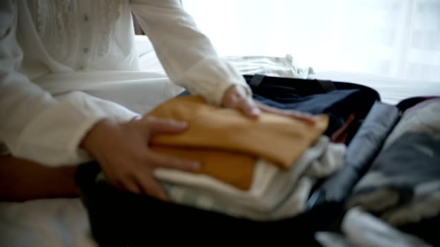 Woman packing travel luggage
