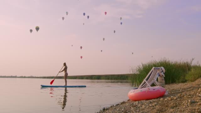 stockvideo's en b-roll-footage met slo mo vrouw paddlesurfen op een meer - peddel