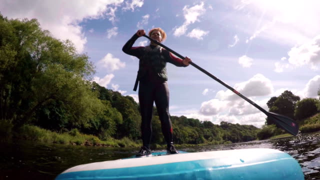 woman paddleboarding - diving suit stock videos and b-roll footage
