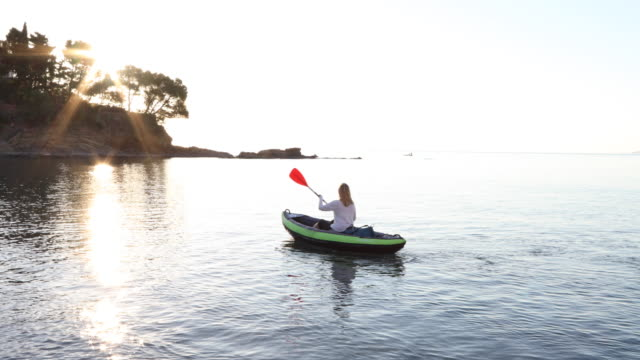 woman paddles inflatable kayak across calm bay, sunrise - pedal pushers stock videos & royalty-free footage