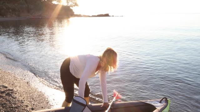 Woman paddles inflatable kayak across calm bay, sunrise