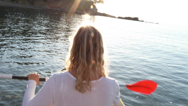 vídeos y material grabado en eventos de stock de woman paddles inflatable kayak across calm bay, sunrise - barco de remos