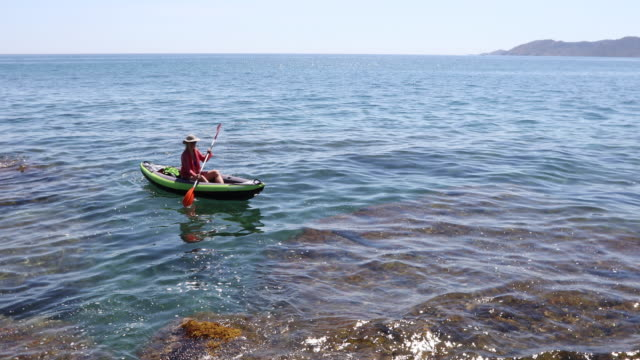 woman paddles inflatable kayak across calm sea lagoon - one mature woman only stock videos & royalty-free footage