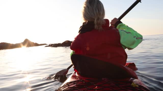 woman paddles kayak on calm sea, thru sea kelp - カナダ ビクトリア市点の映像素材/bロール