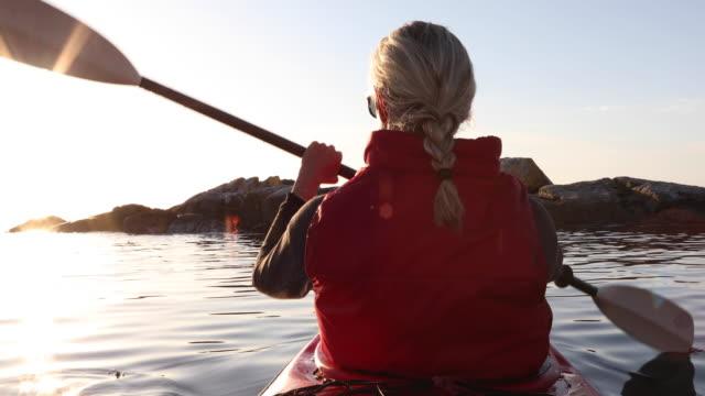 woman paddles kayak on calm sea, thru sea kelp - 55 59 jahre stock-videos und b-roll-filmmaterial