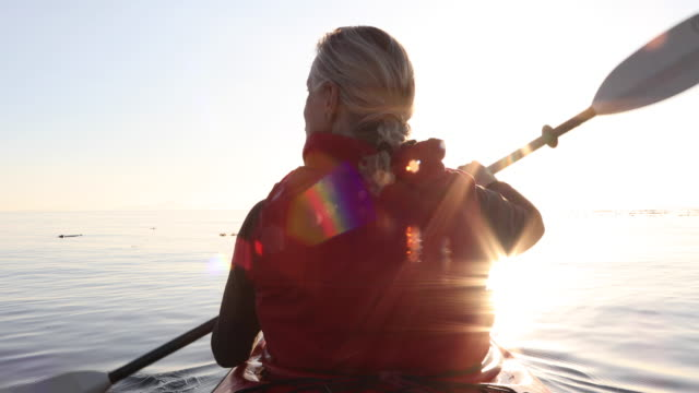 Woman paddles kayak on calm sea, thru sea kelp