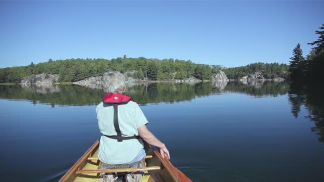MS POV Woman paddling canoe on quiet wilderness lake / Killarney, Ontario, Canada