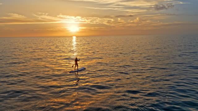 AERIAL femme pagayant sur son SUP en mer au soleil couchant doré