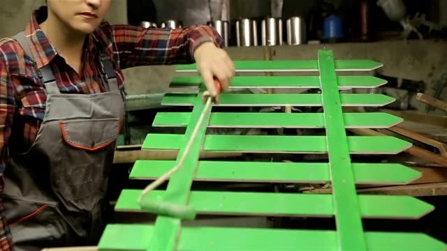Woman paint wooden wheel in workshop