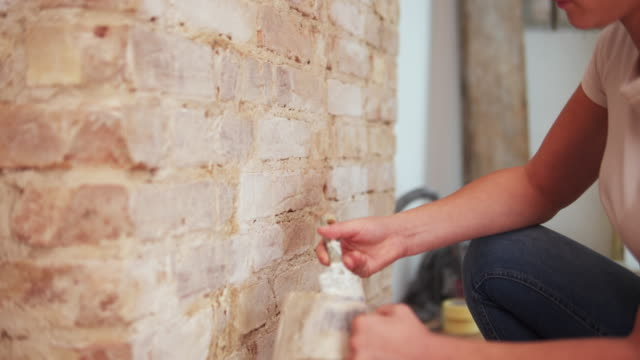 woman painting a brick wall with lime water. - diy stock videos & royalty-free footage