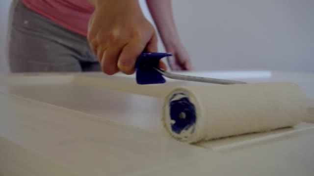 Woman painting a door.