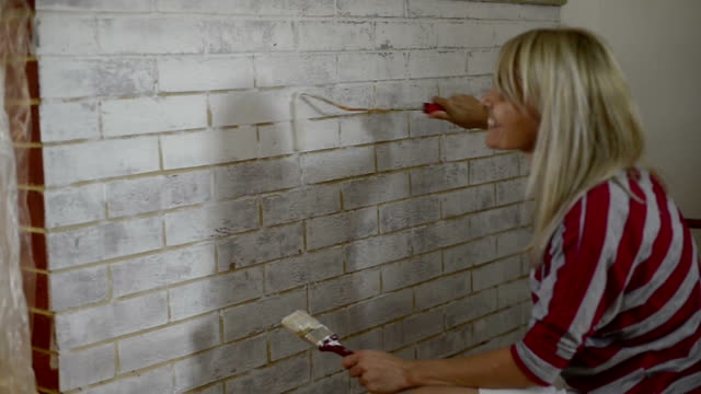 Woman painting brick wall with paint roller.Home decorating ideas.