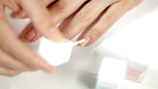 Woman painting fingernails