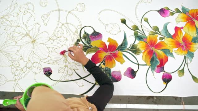 woman painting in a batik workshop - batik stock videos and b-roll footage