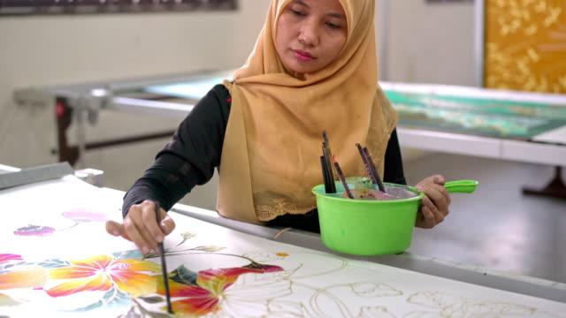 woman painting in a batik workshop - artist stock videos & royalty-free footage