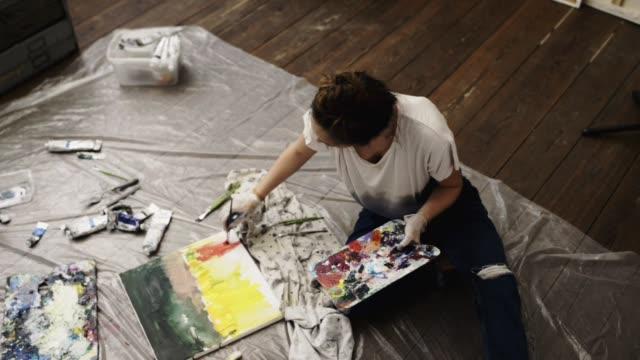 woman painting in artist studio. - pinsel stock-videos und b-roll-filmmaterial