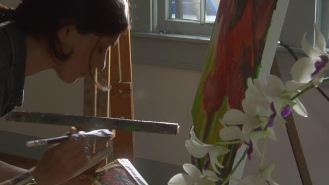 PAN CU Woman painting in studio in garden, Orlando, Florida, USA