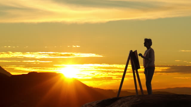 Woman painting landscape picture in sunset.