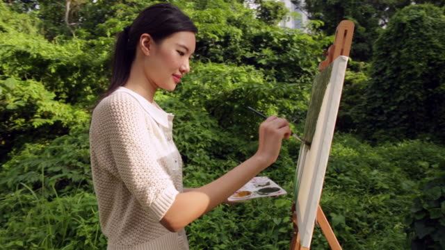 ms woman painting on an easel outdoors. - pittore video stock e b–roll