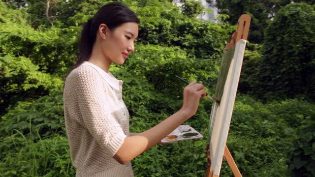 vidéos et rushes de ms woman painting on an easel outdoors. - toile à peindre